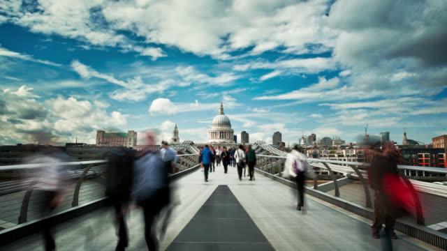 pedestrians scurry along the millennium bridge in london. - london millennium footbridge stock videos and b-roll footage