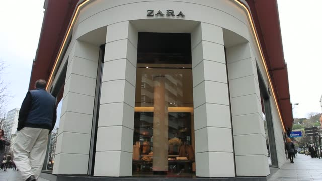 vídeos de stock, filmes e b-roll de pedestrians sheltering from the rain with umbrellas pass the original zara fashion store operated by inditex sa which opened in 1975 in la coruna... - inauguração de loja