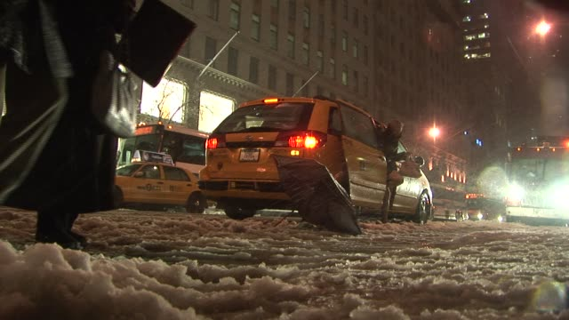 Pedestrians stepping through slush to cross road New York Available in HD