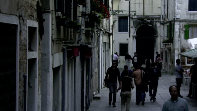 pedestrians stroll along the streets of a ghetto neighborhood in venice. available in hd. - ghetto video stock e b–roll