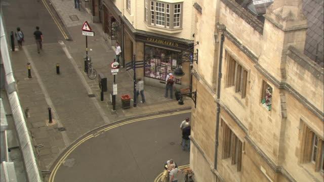 Pedestrians stroll near a store on a street corner in Oxford, England.
