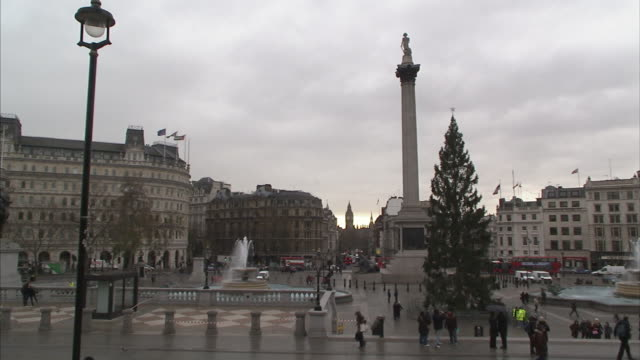pedestrians stroll past a christmas tree in trafalgar square near nelson's column. - overcast stock videos & royalty-free footage