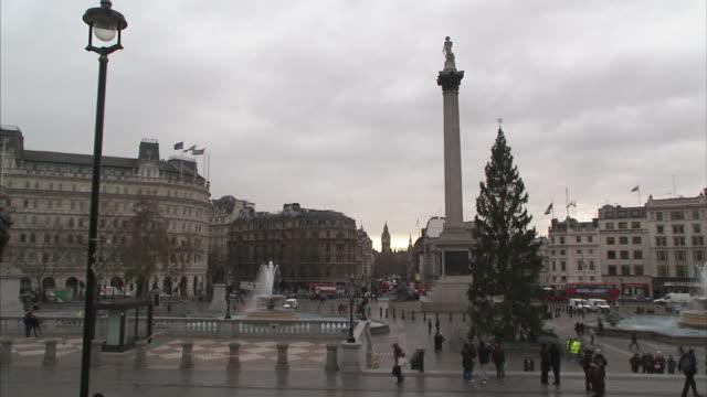 pedestrians stroll past a christmas tree in trafalgar square near nelson's column. - trafalgar square stock-videos und b-roll-filmmaterial