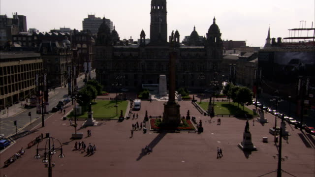Pedestrians stroll though a square in front of the Kelvingrove Museum in Glasgow Scotland. Available in HD.