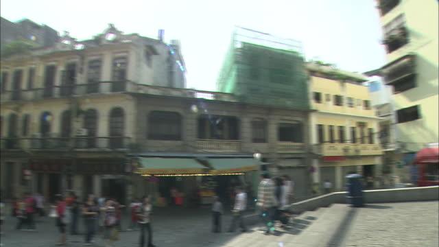 pedestrians stroll through a neighborhood near st. paul's cathedral in macao. - 聖ポール天主堂跡点の映像素材/bロール