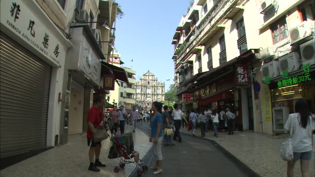 Pedestrians stroll through a neighborhood near St. Paul's Cathedral in Macao.