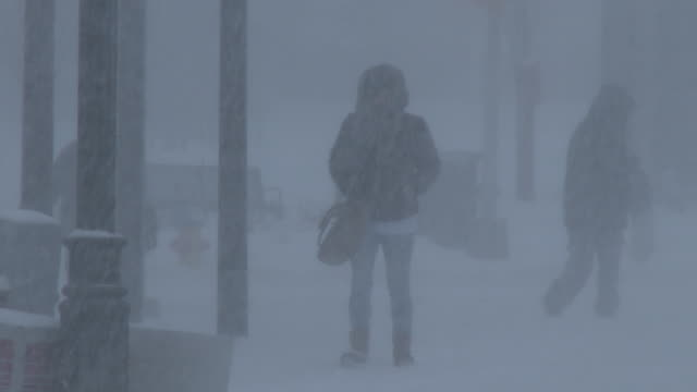 Pedestrians struggle to walk in deep snow as powerful winds and heavy snow combine to create whiteout conditions during an intense blizzard in...
