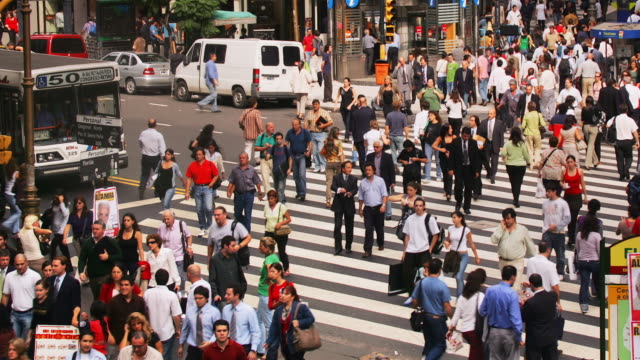 stockvideo's en b-roll-footage met pedestrians use a crosswalk as traffic flows on a busy city street, buenos aires, argentina. - zuid amerika