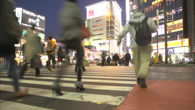 Pedestrians use a crosswalk in Shinjuku at night