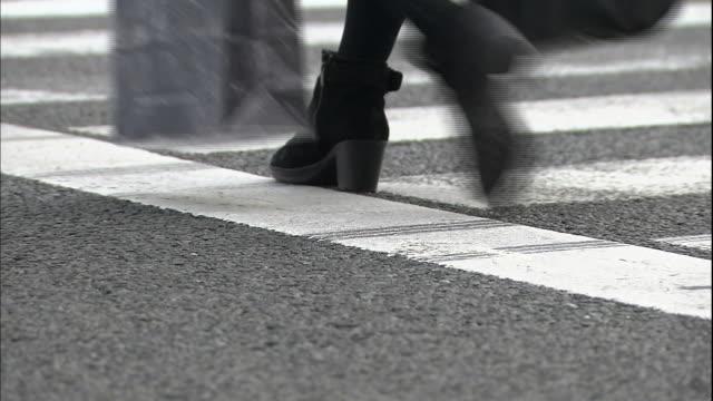pedestrians use a crosswalk on a city street. - randoseru stock videos & royalty-free footage