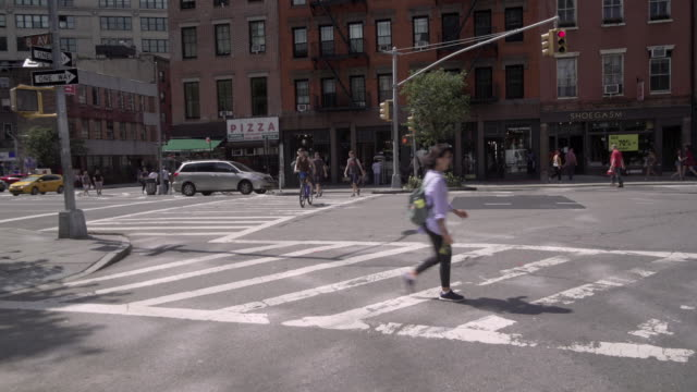 Pedestrians use crosswalk on city street. Camera moves from one corner to another via car mount.