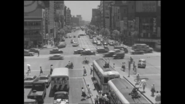 vidéos et rushes de pedestrians use crosswalks as vehicles move through the sukiyabashi intersection. - ligne de tramway