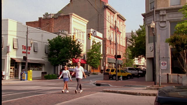 vídeos de stock, filmes e b-roll de pedestrians use crosswalks at intersections on a street in wilmington, north carolina. - wilmington carolina do norte