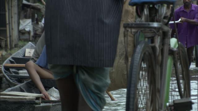 pedestrians wade along a flooded street. available in hd. - bangladesch stock-videos und b-roll-filmmaterial