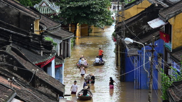 pedestrians wade through a flooded street in hoi an, vietnam. - nautical vessel stock videos & royalty-free footage