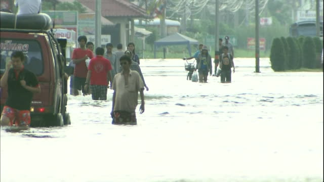 Pedestrians wade through flood waters as a vehicle moves slowly past on an Ayutthaya street