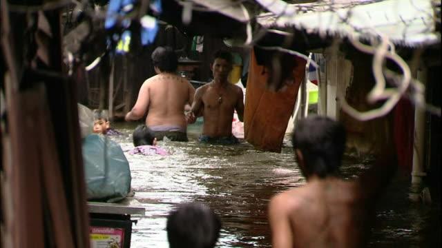 vidéos et rushes de pedestrians wade through flood waters in an alley. - bangkok