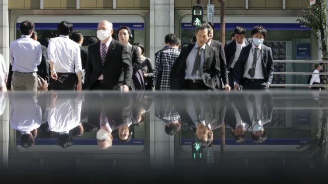 Pedestrians wait to cross a road in front of an electronic stock board outside a securities firm in Tokyo Japan on Wednesday Oct 18 Pedestrians are...