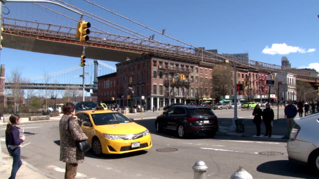 Pedestrians wait to cross Old Fulton Street in the historic DUMBO district of Brooklyn NY