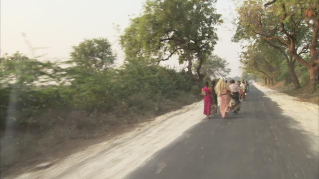 pedestrians walk a long a street in india. - fahrradtaxi stock-videos und b-roll-filmmaterial