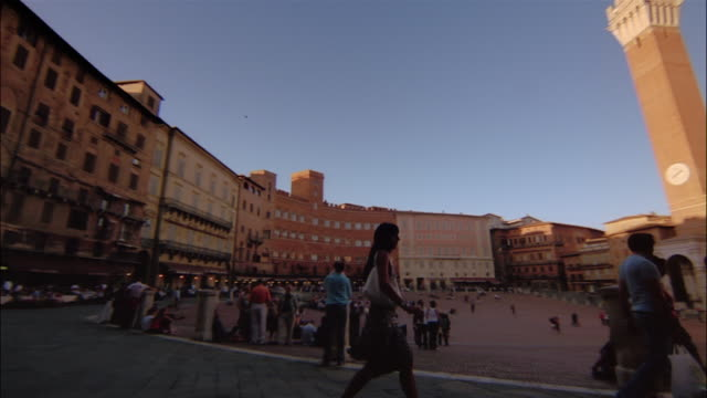 pedestrians walk across a plaza to torre del mangia and palazzo pubblico in siena, tuscany, italy. - palazzo pubblico stock videos and b-roll footage