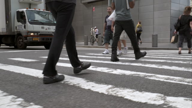 Pedestrians walk across crosswalk on busy New York City street on a clear day.