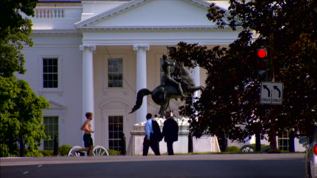 pedestrians walk across lafayette square in front of the white house in washington, dc. - lafayette square washington dc stock videos & royalty-free footage