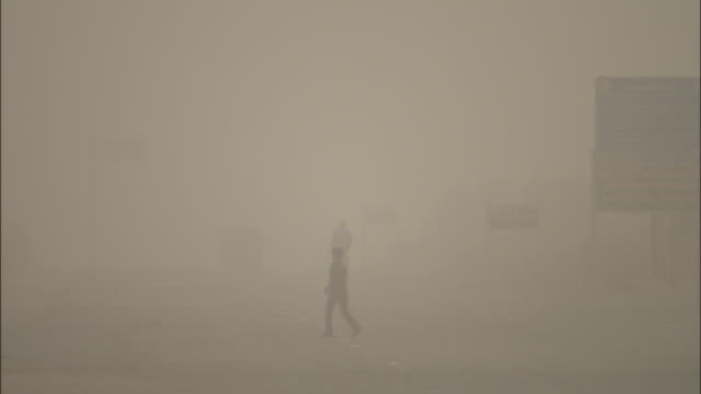 pedestrians walk across road during sand storm in takla makan desert, shinjang uyghur autonomous region of chinese central asia - luftverschmutzung stock-videos und b-roll-filmmaterial