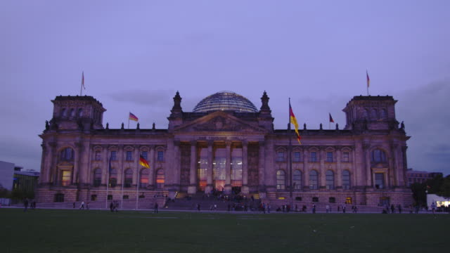Pedestrians walk across the expansive lawn in front of the Reichstag.