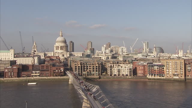 Pedestrians walk across the Millennium Bridge as a ferry cruises the River Thames. Available in HD.