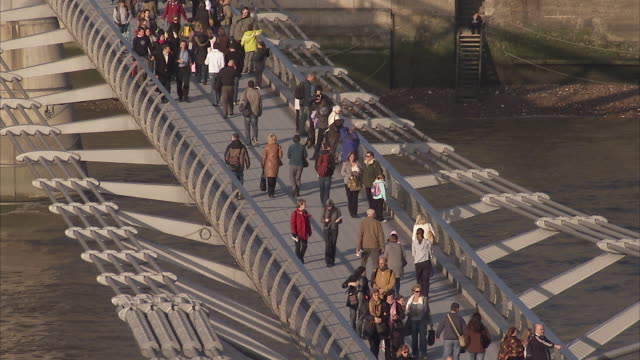 Pedestrians walk across the Millennium Bridge. Available in HD.