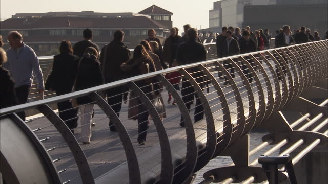 Pedestrians walk across the Millennium Bridge London Available in HD.
