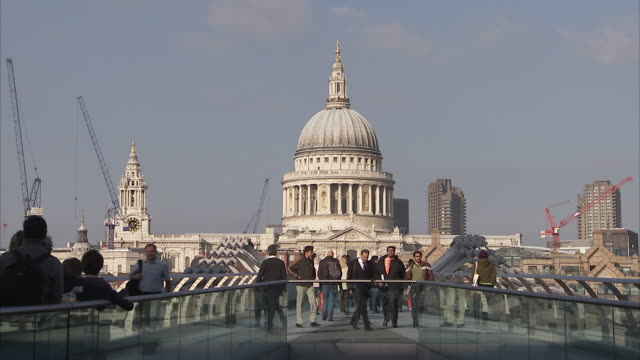 Pedestrians walk across the Millennium Bridge. London Available in HD.