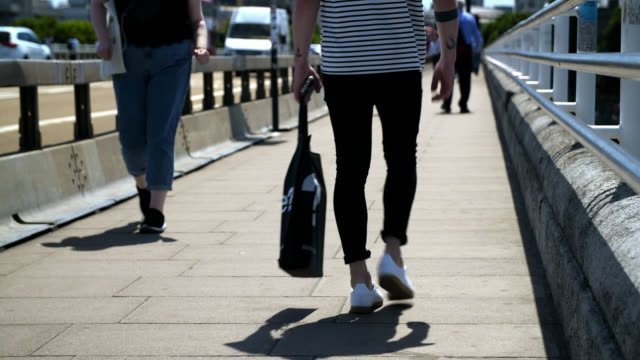 pedestrians walk across waterloo bridge, london - menschliche gliedmaßen stock-videos und b-roll-filmmaterial