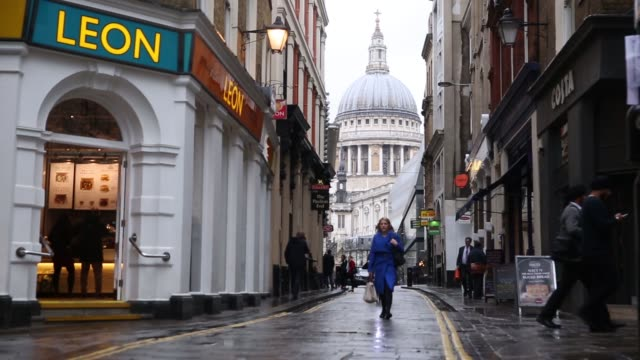 Pedestrians walk across wet pavements backdropped by St Paul's cathedral in the City of London United Kingdom on Wednesday March 9 2016