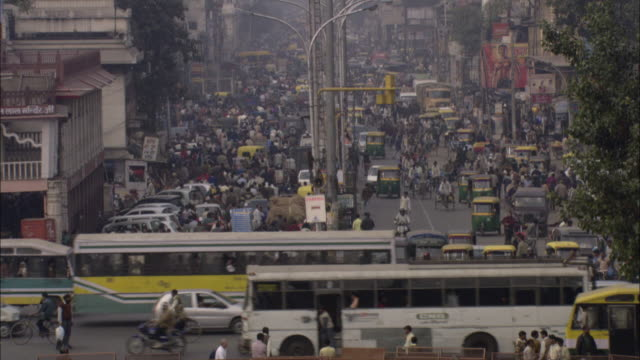 pedestrians walk along a busy urban street with many vehicles on the road. - population explosion video stock e b–roll