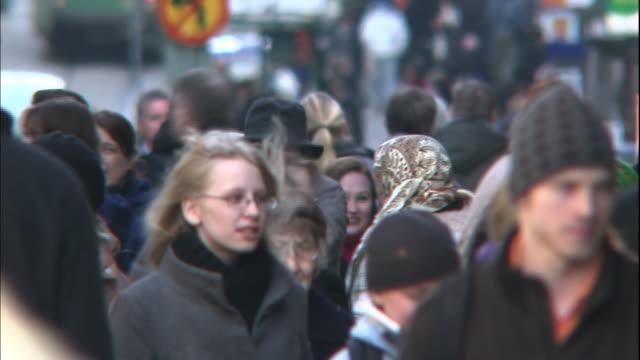 vídeos de stock, filmes e b-roll de pedestrians walk along a city sidewalk. - finlândia