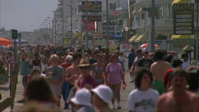 Pedestrians walk along a crowded beach.