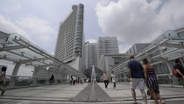 Pedestrians walk along a footbridge in front of commercial buildings in Yokohama Kanagawa Prefecture Japan on Saturday July 27 Various high angle...