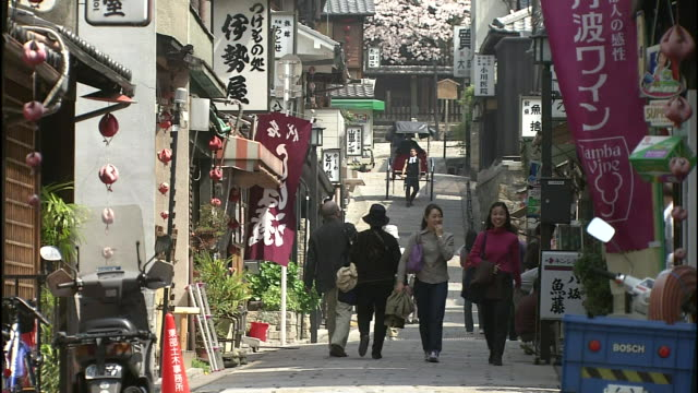 pedestrians walk along a narrow street at the foot of the five-story yasaka pagoda in kyoto, japan. - gion stock videos and b-roll footage