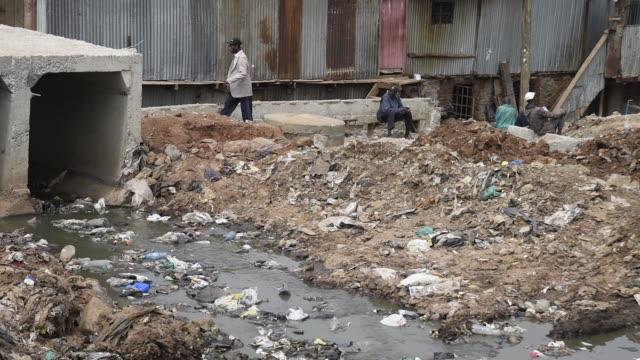pedestrians walk along a railway line lined with new homes for slum dwellers in the center of the kibera slum in nairobi kenya on friday july 21... - スラム街点の映像素材/bロール