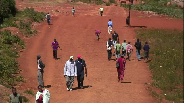 pedestrians walk along a red dirt road. - village stock videos & royalty-free footage