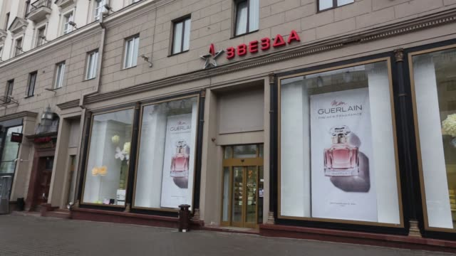 pedestrians walk along a shopping street in central minsk, belarus, on wednesday, march 15 hugo boss ag, national flags of belarus fly outside the... - hugo boss stock videos & royalty-free footage