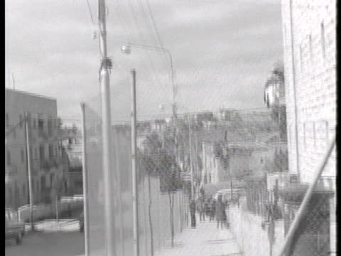 stockvideo's en b-roll-footage met pedestrians walk along a sidewalk enclosed by barbed wire fence outside the courthouse where former gestapo official adolf eichmann awaits sentencing. - prikkeldraad