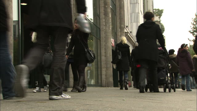 pedestrians walk along a sidewalk in berlin. - pavement stock-videos und b-roll-filmmaterial
