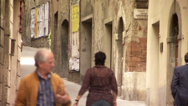pedestrians walk along a steep, narrow street, montepulciano. available in hd. - montepulciano stock videos & royalty-free footage
