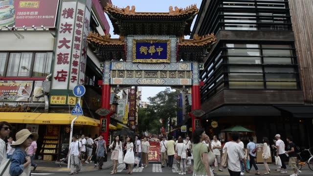 pedestrians walk along a street at the yokohama chinatown in yokohama city, kanagawa prefecture, japan, on saturday, july 27 pedestrians walk past... - 中華街点の映像素材/bロール