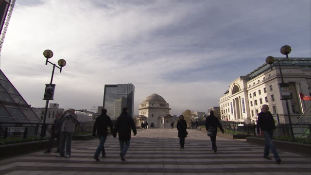 Pedestrians walk along Centenary Square before the Hall of Memory Birmingham England Available in HD.