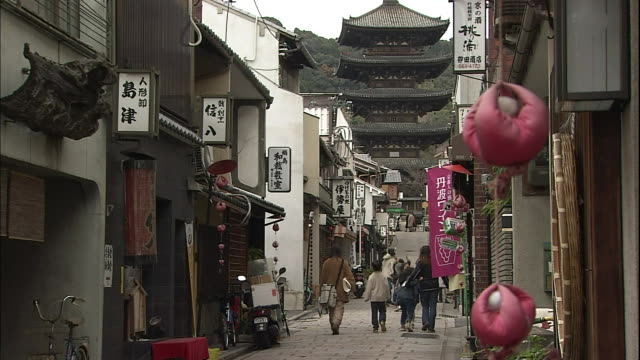 pedestrians walk along narrow streets near the yasaka pagoda in kyoto. - kyoto temple stock videos and b-roll footage