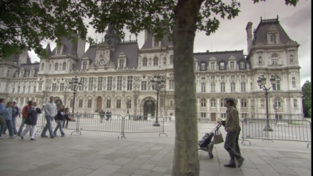 pedestrians walk along past the hotel de ville in paris. - hotel de ville paris stock videos & royalty-free footage